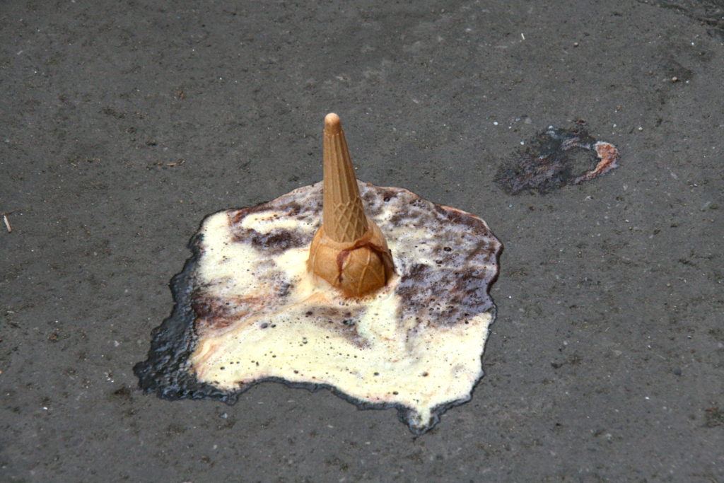 Ice cream cone fallen upside down on a sidewalk.